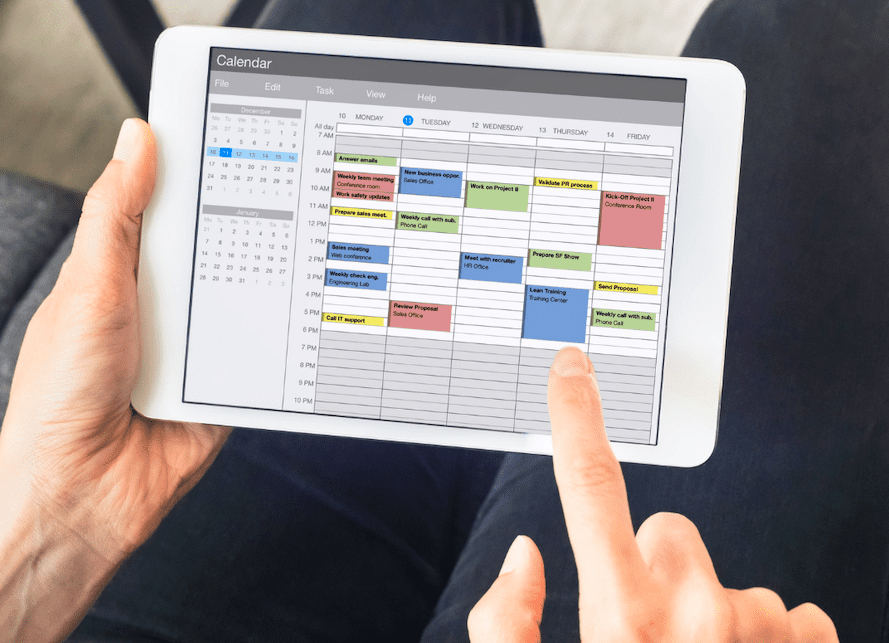 Fingers Hover Over Tablet Displaying A Weekly Schedule