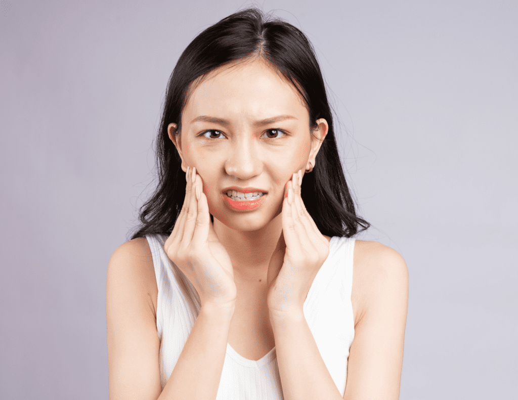 Woman Experiences Wisdom Tooth Discomfort As She Cradles The Side Of Her Face With Both Hands